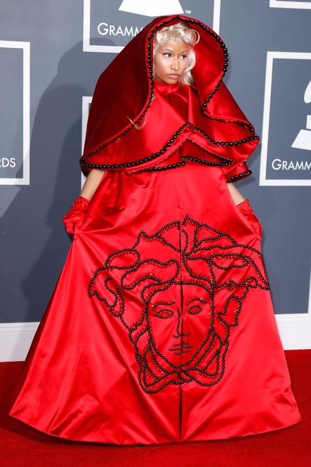 Nicki Minaj posiert in einem roten Umhang-Kleid auf dem roten Teppich.
