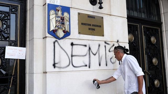 Mann sprayt an Wand.