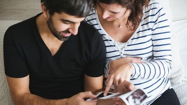 Ein Mann und eine schwangere Frau sitzen auf dem Sofa.