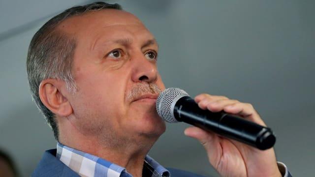 Il president tirc Recep Tayyip Erdogan cun microfon.