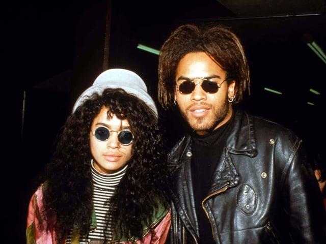 Zwei People of Color, beide mit vollem dunklen haar und Sonnenbrille mit runden Gläsern schauen in die Kamera. Die Frau links trägt einen Hut. Der Mann rechts eine Lederjacke