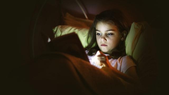 Ein Mädchen liest im Bett ein Buch.