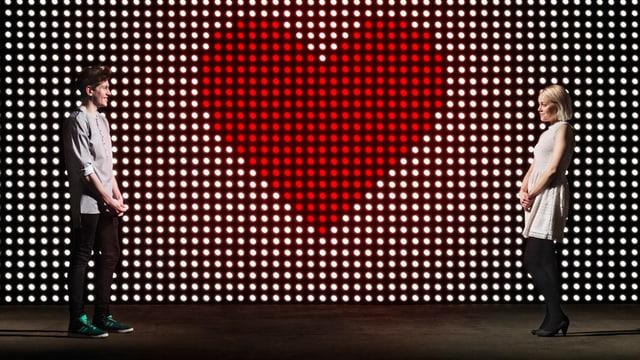 Eine Frau und ein Mann stehen sich gegenüber. Vor einer Leuchttafel, auf der ein Herz zu sehen ist.