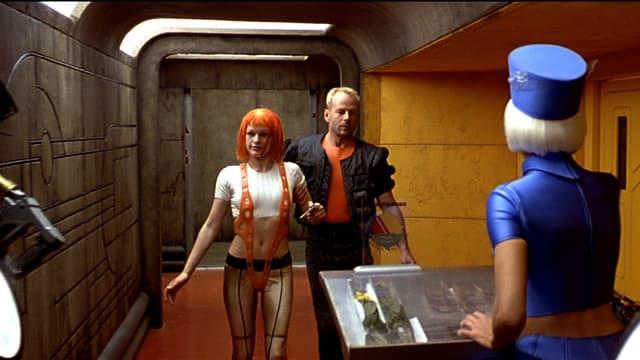 Eine Frau und ein Mann gehen Arm in Arm zu einem Desk, an dem eine Frau steht.