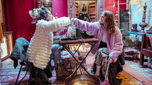 Zwei Frauen in flauschigen Mänteln sitzen an einem Tisch in einem üppig deokorierten Laden.