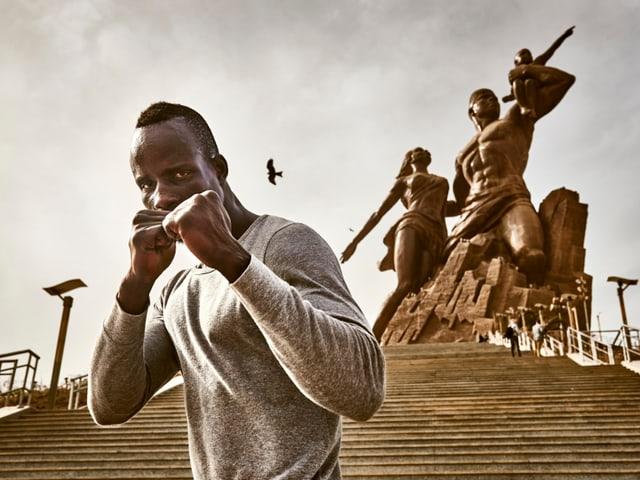 Mann steht vor Statue und hält Fäuste zum Kampf bereit