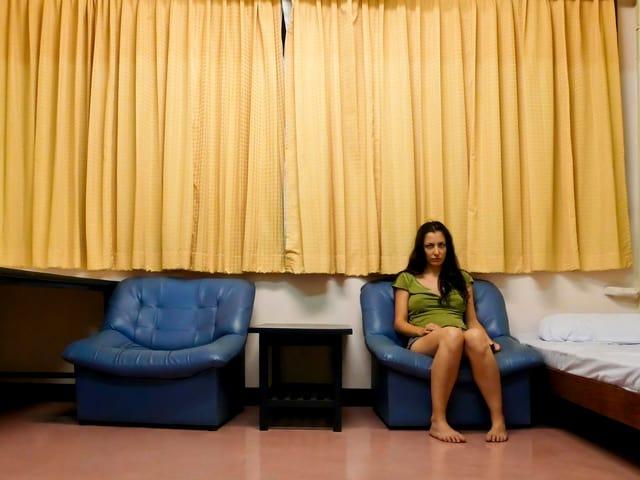 Frau sitzt zusammengesunken in einem Sessel, Vorhänge, gelb, sind geschlossen