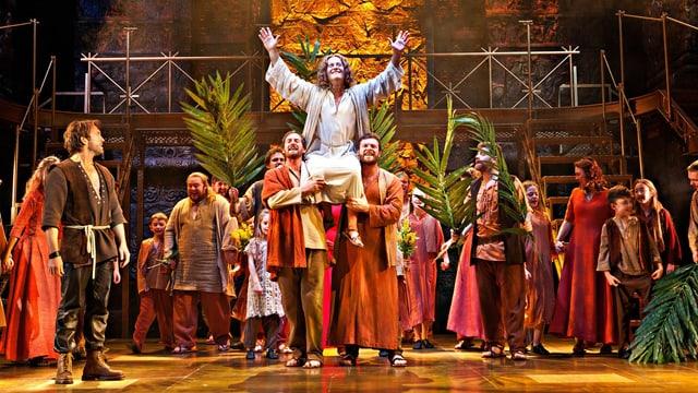 Jesus wird auf Händen getragen und winkt lächelnd in die Menge.