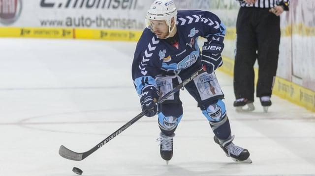Kevin Clark im blauen Shirt der Hamburg Freezers führt den Puck übers Eis.