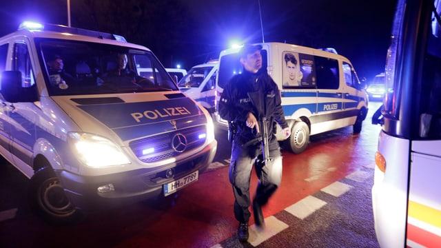 Polizeifahrzeuge stehen mit Blaulicht herum, ein bewaffneter Polizist davor, Szene bei Nacht.
