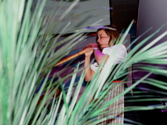 Lisa Stoll hinter grünen Blättern einer Palme.