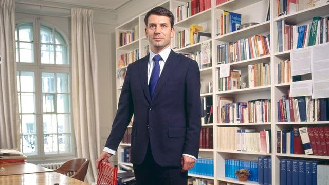 Ein Mann in Anzug und Krawatte steht vor einem Bücherregal neben einem Tisch.