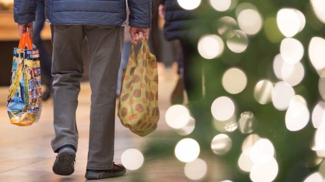 Mann hält Einkaufstüten, Weihnachtsbaum daneben.
