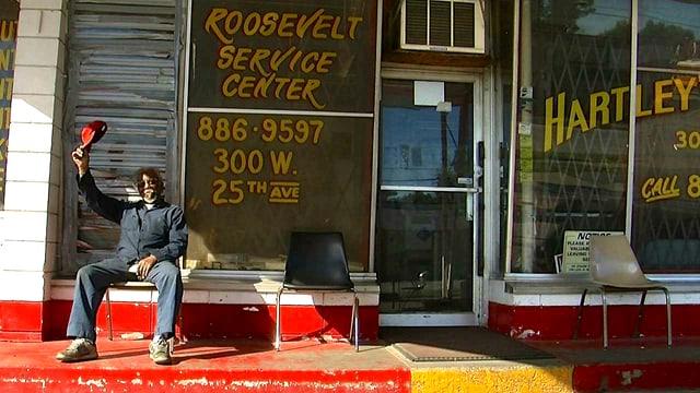 Ein schwarzer Mann sitzt vor einem Laden auf einem Stuhl und winkt mit seinem Hut.