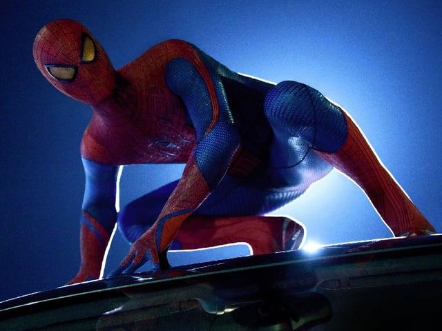 Spiderman auf einem Autodach.