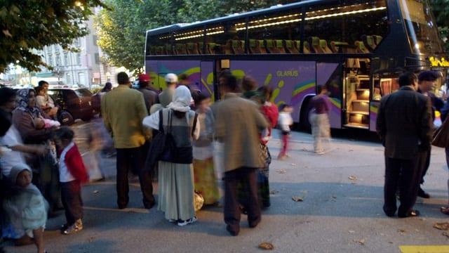 Fugitivs che spetgan davant in bus.