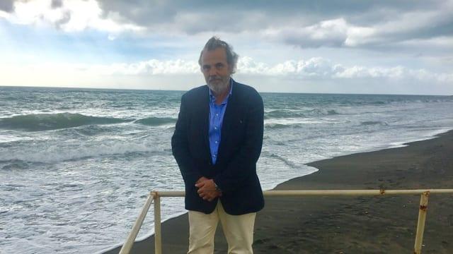 Muzzarelli posiert auf seinem Strand. Im Hintergrund graue Wolken und Wind zerzaust sein Haar.