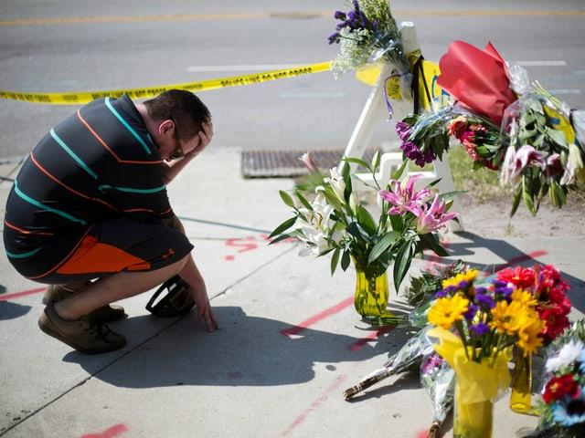 Ein Mann kniet am Boden, vor ihm gelbes Polizeiabsperrband. Auf der Strasse stehen Blumensträusse.