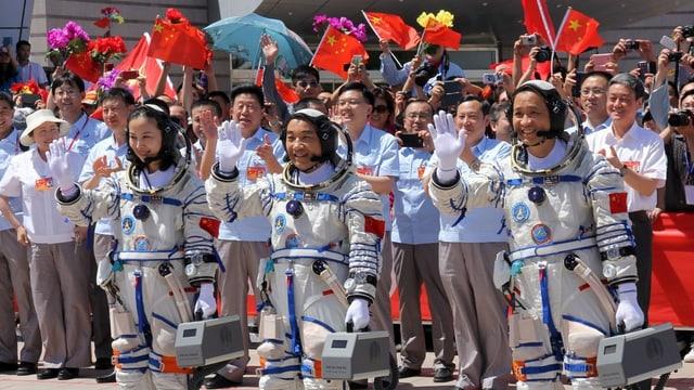 Drei Astronauten stehen winkend vor einer Menschenmenge.