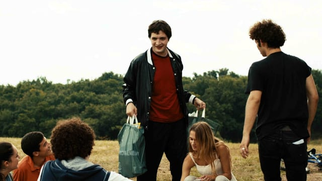 Joseph mit Einkaufstüten stehend vor einer Gruppe sitzender Jugendlicher
