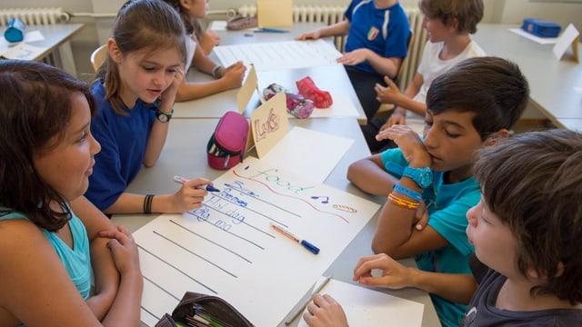 Kinder sitzen zusammen an einem Pult und schreiben englische Wörter auf.