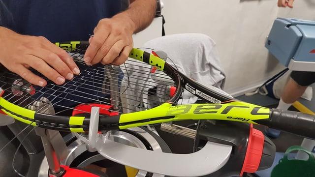 Ein Bespanner arbeitet am Schläger von Rafael Nadal.