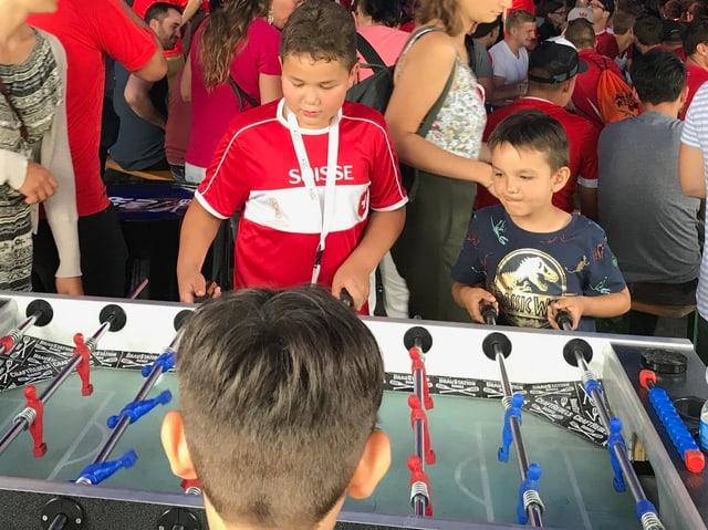 Kinder spielen an einem Fussballtöggelikasten.