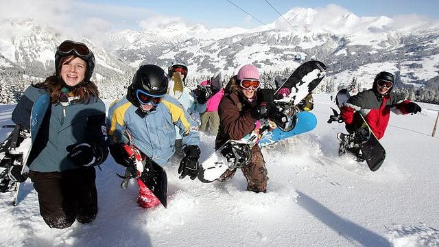 Ein Gruppe Kinder, die sich mit Snowboards und zu Fuss im Tiefschne vergnüngt.