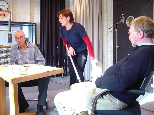 Um einen Tisch mit Mikrofon sitzen zwei Männer, zwischen ihnen steht eine Frau mit Staubsauger in der Hand.
