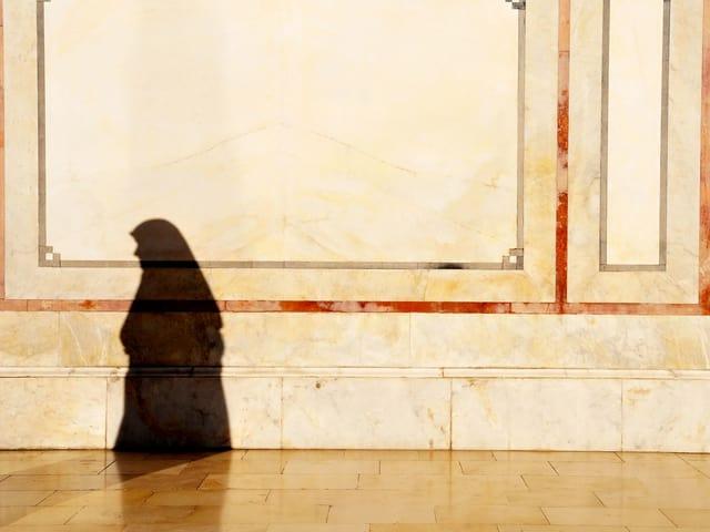 Eine verschleierte Frau wirft einen Schatten an eine dekorierte Hauswand.