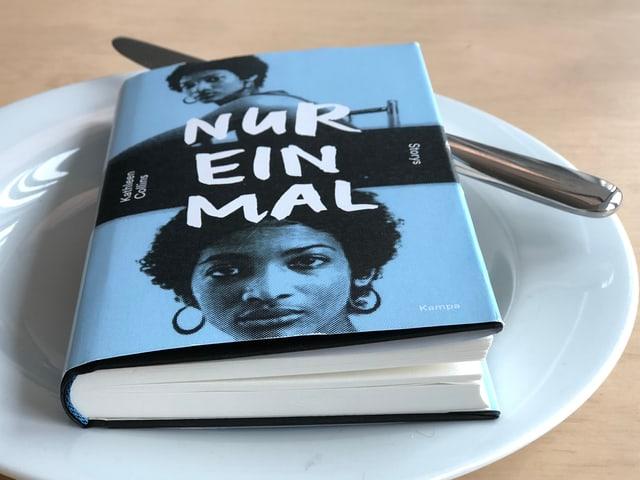 Der Sammelband «Nur einmal» mit Kurzgeschichten von Kathleen Collins liegt auf einem weissen Teller