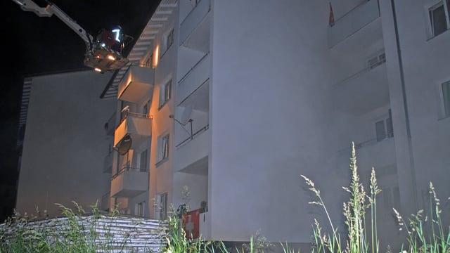 Wohnblock mit einer Drehleiter der Feuerwehr davor.