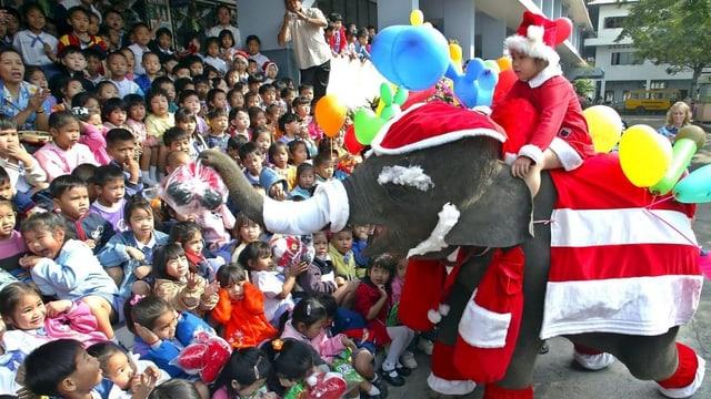 Elefant verkleidet als Weihnachtsmann bringt Kindern einer thailändischen Schule Geschenke.