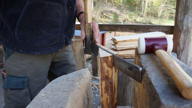 Mann spaltet Holz mit Werkzeug.