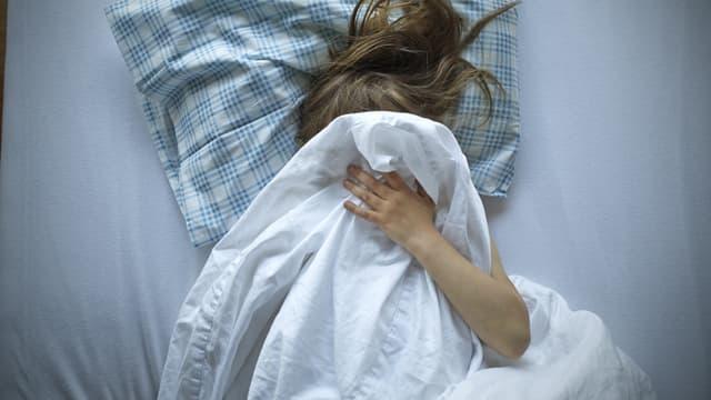 Eine Frau liegt unter der Bettdecke und zieht diese übers Gesicht.