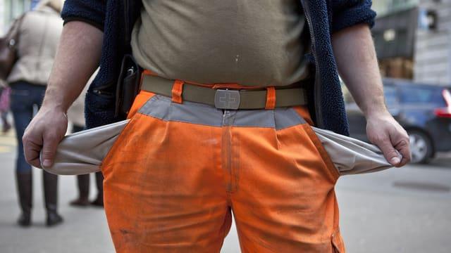 Ein Mann mit oranger Hose zieht die leeren Hosensäcke nach aussen.