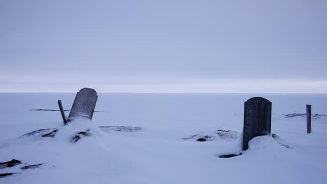 Zwei Grabsteine im Schnee.