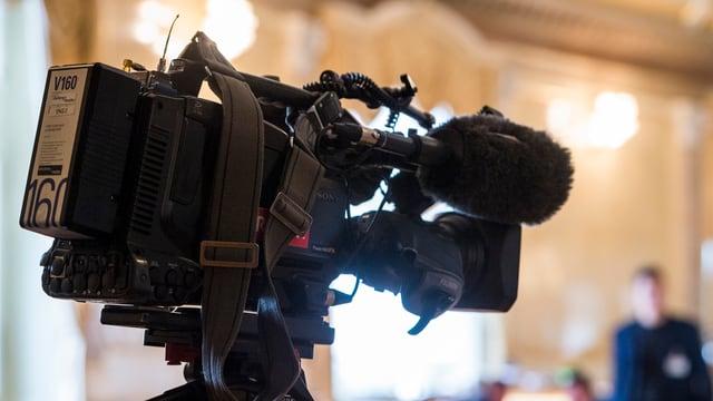Fernsekamera im Vordergrund und verschwommen im Hintergrund ein Raum und eine nicht erkennbare Person