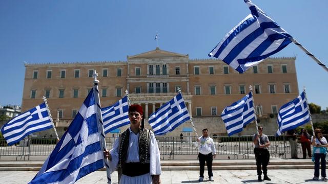 Griechisches Parlament, davor stehen Menschen mit Flaggen in der Hand