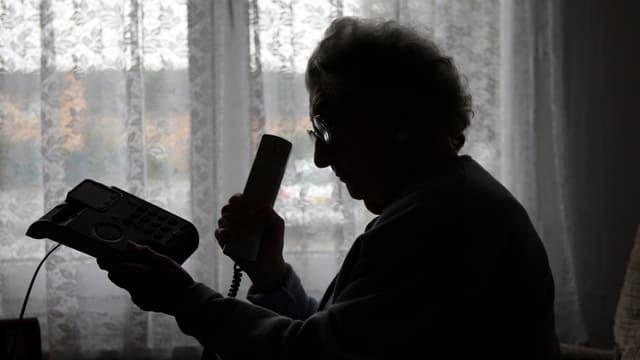 Silhouette einer älteren Frau, die den Telefonhörer abhebt
