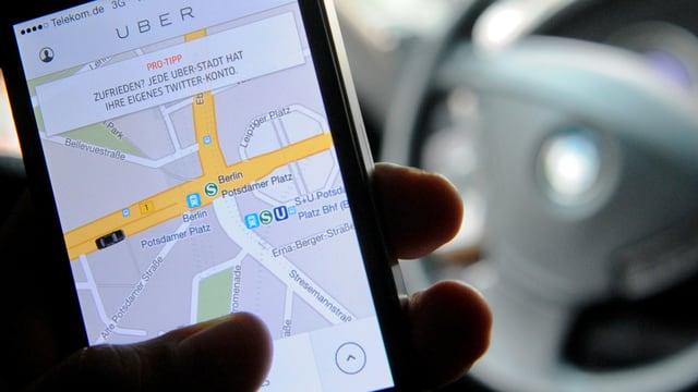 Smartphone mit der Uber-App vor einem Lenkrad.