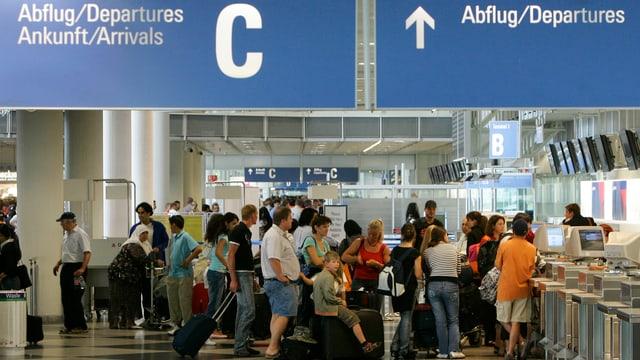 Flugpassagiere stehen an, um ihre Koffer aufzugeben.