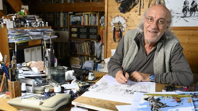ein älterer Herr zeichnet an seinem Schreibtisch