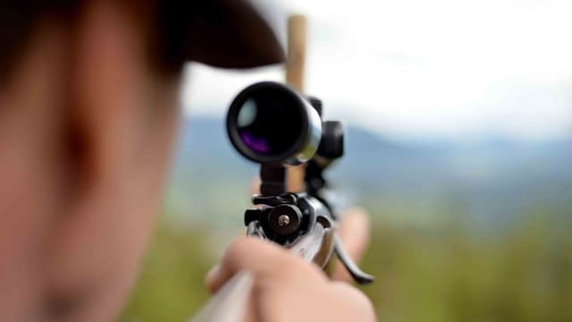 Mann sieht durch Zielrohr eines Gewehrs.