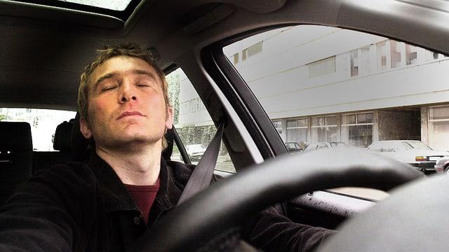 Mann sitzt mit geschlossenen Augen am Steuer eines Autos.