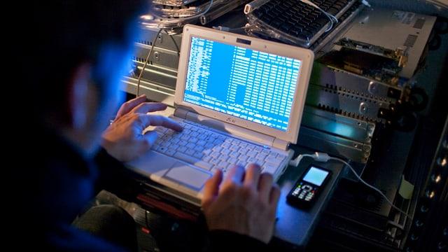 Ein Hacker sitzt im Dunkeln vor einem Computer.
