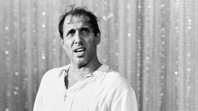 Schwarzweissfoto von Celentano im weissen Hemd vor einem Bühnenvorhang.