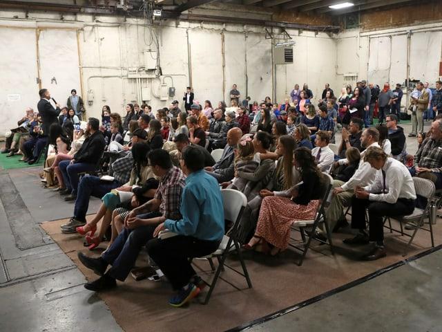 Raum gefüllt mit Menschen, die nahe aufeinander sitzen