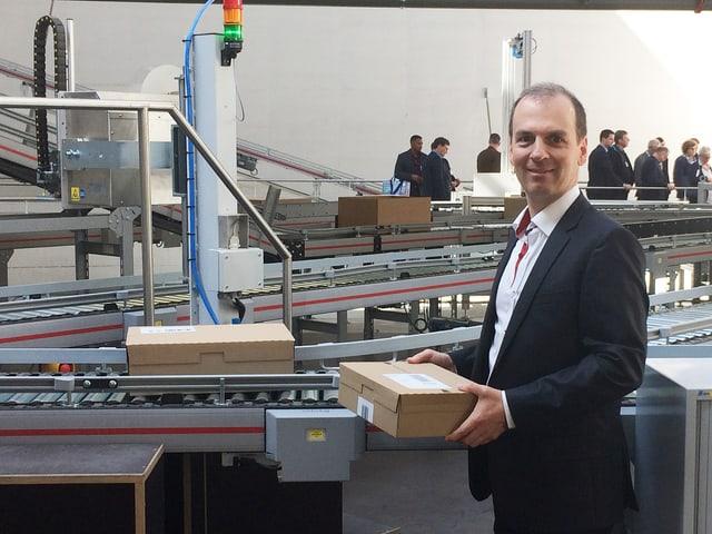 Geschäftsmann Roland Brack an einer der Maschinen im Logistikzentrum in Willisau.