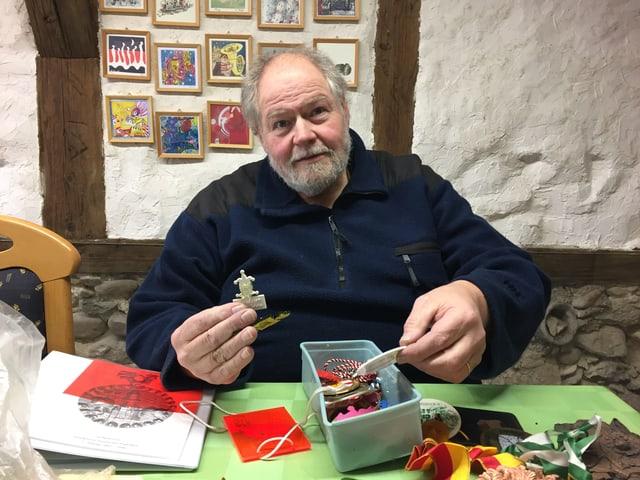 Mann hinter Tisch mit Plaketten.
